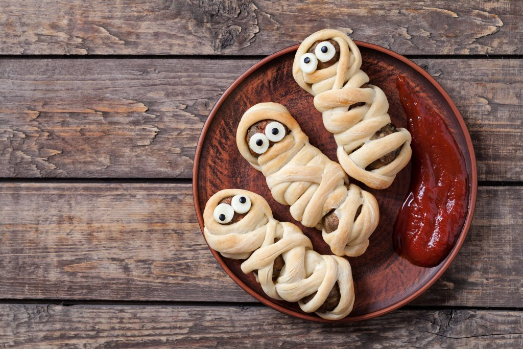 Mummy sausages scary halloween party food decoration wrapped in dough with blood sauce on clay dish.