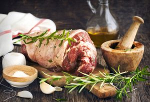 Raw boneless lamb leg with garlic and rosemary on wooden backgro
